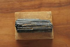 Black tourmaline stone on a background of natural wood American. Black walnut. Mineral collection stones. Stone is a sherl tourmaline. Black Crystal stock photo
