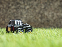 A black toy car park on green grass field. Stock Photo
