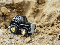 A black toy car park in sandbox. Royalty Free Stock Image