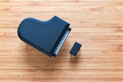 Black toy grand piano on a wooden floor with stool standing near it. Top view. Stock Photo