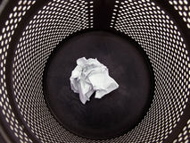 Black trash can. Close-up of a black trash can with a paper in it Stock Photo