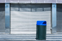 Black Trash can with blue cap against industrial metal door Royalty Free Stock Images