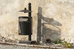 Black trash can near the wall. Royalty Free Stock Images