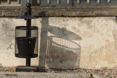 Black trash can near the wall. Royalty Free Stock Photos