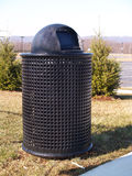 Black trash can by trees. A black trash can by trees Royalty Free Stock Photo