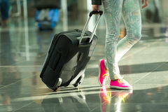Black travel bag on wheels in hand. Black travel bag or suitcase on wheels in hand and female legs in floral jeans and bright pink gumshoes on feet on grey tile Royalty Free Stock Image