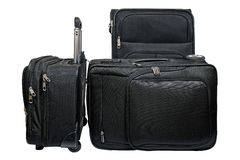 Black travel luggage set. Set of three matching black suitcases of different sizes with telescoping metal handles and wheels made from a black ballistic nylon Stock Photo