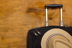 Black traveler suitcase and a straw hat Stock Image