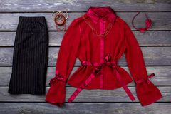 Black trousers and red blouse, flat lay. Striped pants, polyester blouse and accessories royalty free stock photography