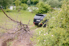Black Truck Hauling Dead Tree Branch Through Field. Black SUV Truck Dragging Dead Bare Tree Branch Through Field Near River Stock Image