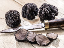 Black truffles on a old wooden table. stock photo