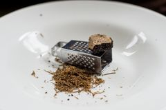 Black truffles on a plate. Shaved transylvanian truffles on a white plate Stock Image