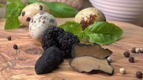 Black truffles and quail eggs on a wooden board. Circular movement of the camera around of black truffles, quail eggs and basil on a wooden board stock video