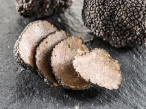 Black truffles and truffle slices on the graphite board royalty free stock image