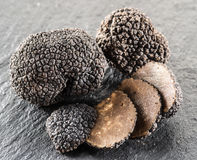 Black truffles and truffle slices. Black truffles and truffle slices on the graphite board stock photo