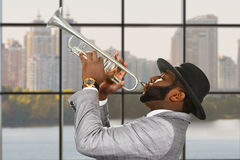 Black trumpeter performing at daytime. Afro trumpeter on urban background. Trumpeter performing with passion. Stylish musician plays music Royalty Free Stock Photo