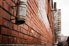 Black tube on a brick house wall (drain water) Royalty Free Stock Images