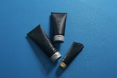 Black tubes with space for design on wet color surface. Men`s cosmetic products. Black tubes with space for design on wet color surface, flat lay. Men`s cosmetic royalty free stock image
