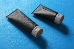 Black tubes on wet color surface. Men`s cosmetic products. Black tubes on wet color surface, space for design. Men`s cosmetic products stock photos