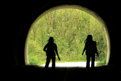 Black tunnel and people. Two girls (best friends) rolling at road cross the dark black tunnel. Horizontal color photo Stock Photography