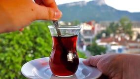 Black turkish tea. Stirring black Turkish tea in a glass with a view on Taurus mountains in Kemer, Turkey stock video