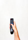Black TV remote control in mens hand on a light gray background Royalty Free Stock Photo