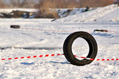 Black tyre on snowy racetrack. Black rubber tyre marks the edge of a winter, snowy off-road racetrack Stock Photography