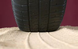 Black tyre and track on sand Stock Photos