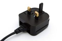Black UK plug over white Royalty Free Stock Image