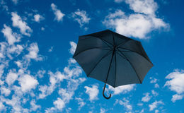 Black umbrella against a cloudy sky Royalty Free Stock Photography