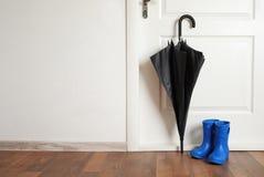 Black umbrella and gumboots. On floor near door Royalty Free Stock Photography
