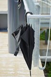 Black umbrella hanging on the railing outside Stock Image