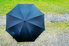 Black umbrella place on grass background. Front view of black umbrella on grass. Background royalty free stock photos