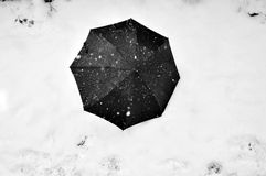 Black umbrella on the snow. A black umbrella on a field covered by snow while snowing Royalty Free Stock Images