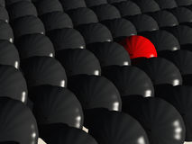 Black umbrellas with one  red umbrella Stock Image
