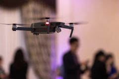 Black unmanned quadrocopter took off in a banquet hall with people on a blurred background. royalty free stock photography