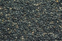 Black unpeeled sesame seeds close up, background royalty free stock photo