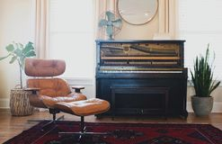 Black Upright Piano Near Orange Glider Chair Stock Photo