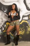 Black Urban girl sexy hooded outfit by graffiti. Sexy urban black girl in boots, bra and hooded jacket standing by graffiti wall Stock Photos