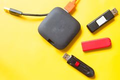 Black USB HUB with usb stick flash drives on yellow background. Top view stock photography