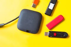 Black USB HUB with usb stick flash drives on yellow background. Top view royalty free stock photography