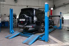 Black used Mitsubishi Pajero stands on the stand wheel alignment convergence of the car in the workshop for repair of vehicles. Novosibirsk, Russia - 08.01.2018 royalty free stock image