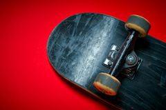 Used skateboard on a red background Royalty Free Stock Images