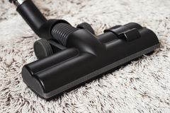 Black vacuum cleaner brush closeup. Close up of the head of a modern vacuum cleaner being used while vacuuming a thick pile white carpet.still life dark tone Royalty Free Stock Photography