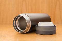 Black vacuum tumbler. On a wood table Stock Photography