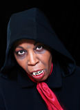 Black vampire. African american vampire in black hooded coat and red scarf ready to pounce on Halloween stock images