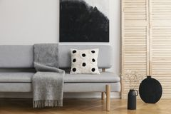 Black vase with cotton flower on the floor of bright trendy living room with grey sofa with pillow and warm blanket, real photo. With copy space and mockup royalty free stock photo