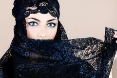 Black veil. Shot of a beautiful asian woman with black veil on face, traditional arabian costume Stock Image
