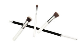 Black velvet ribbon and three makeup brushes on white background Stock Photos