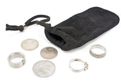 Black velvet sack with silver rings and coins Royalty Free Stock Photos